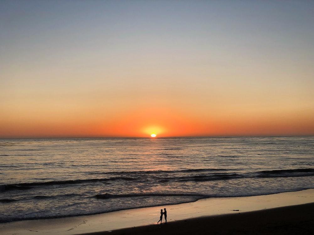 two people standing in seashore