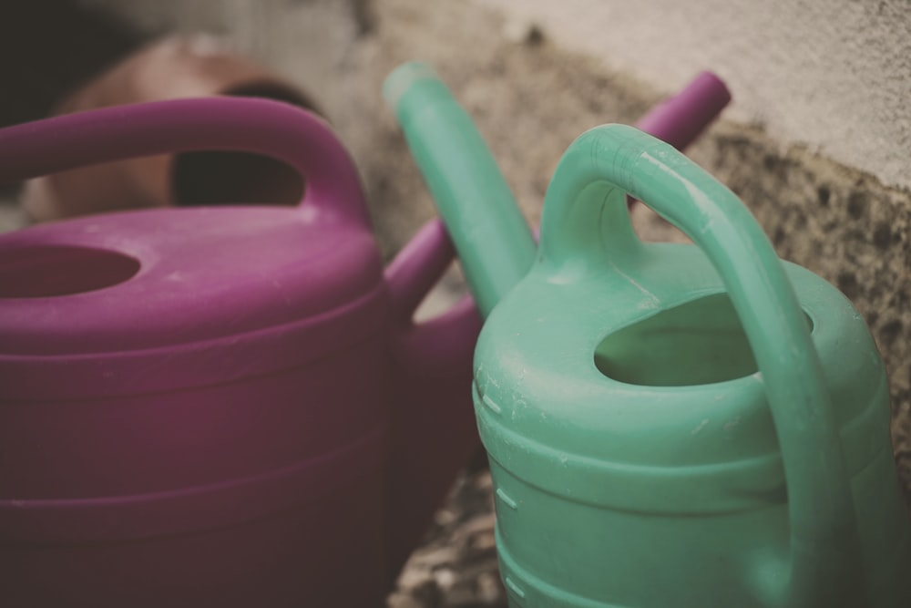 two green and pink watering cans