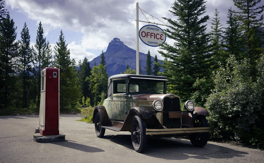 classic vehicle beside red and white telephone booth
