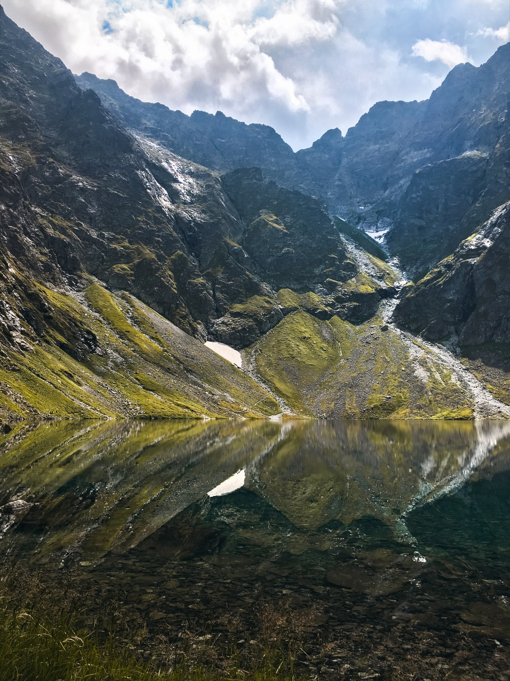 reflection of green mountains on body of water during daytime