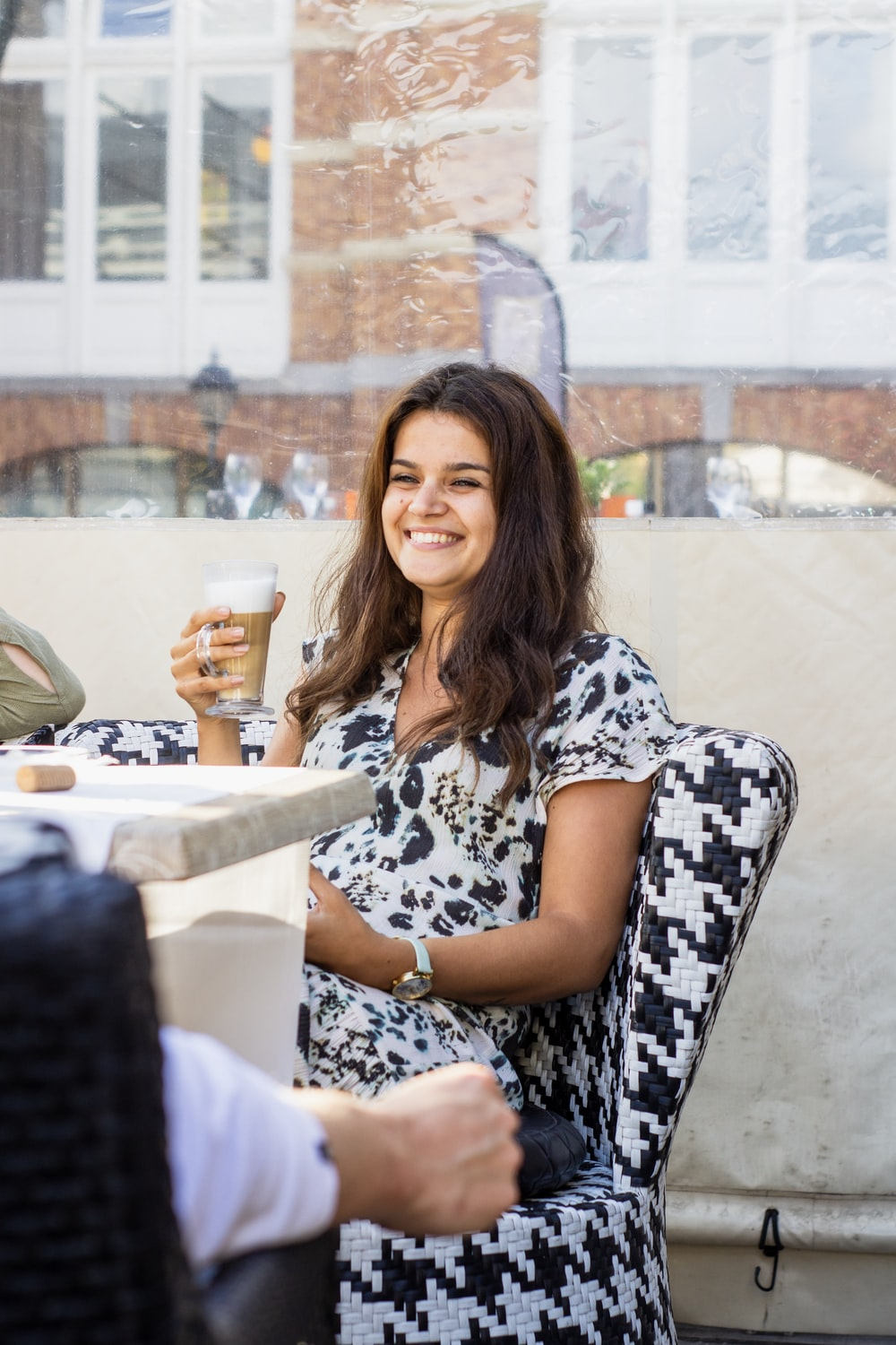 smiling woman holding cup of beverage