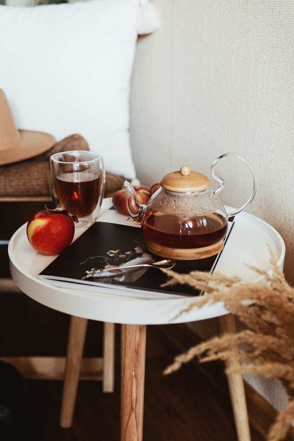 teapot near gray stainless steel teaspoon, red apple fruit, and clear glass mug on round white wooden end table