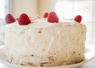 round white icing covered cake with raspberries