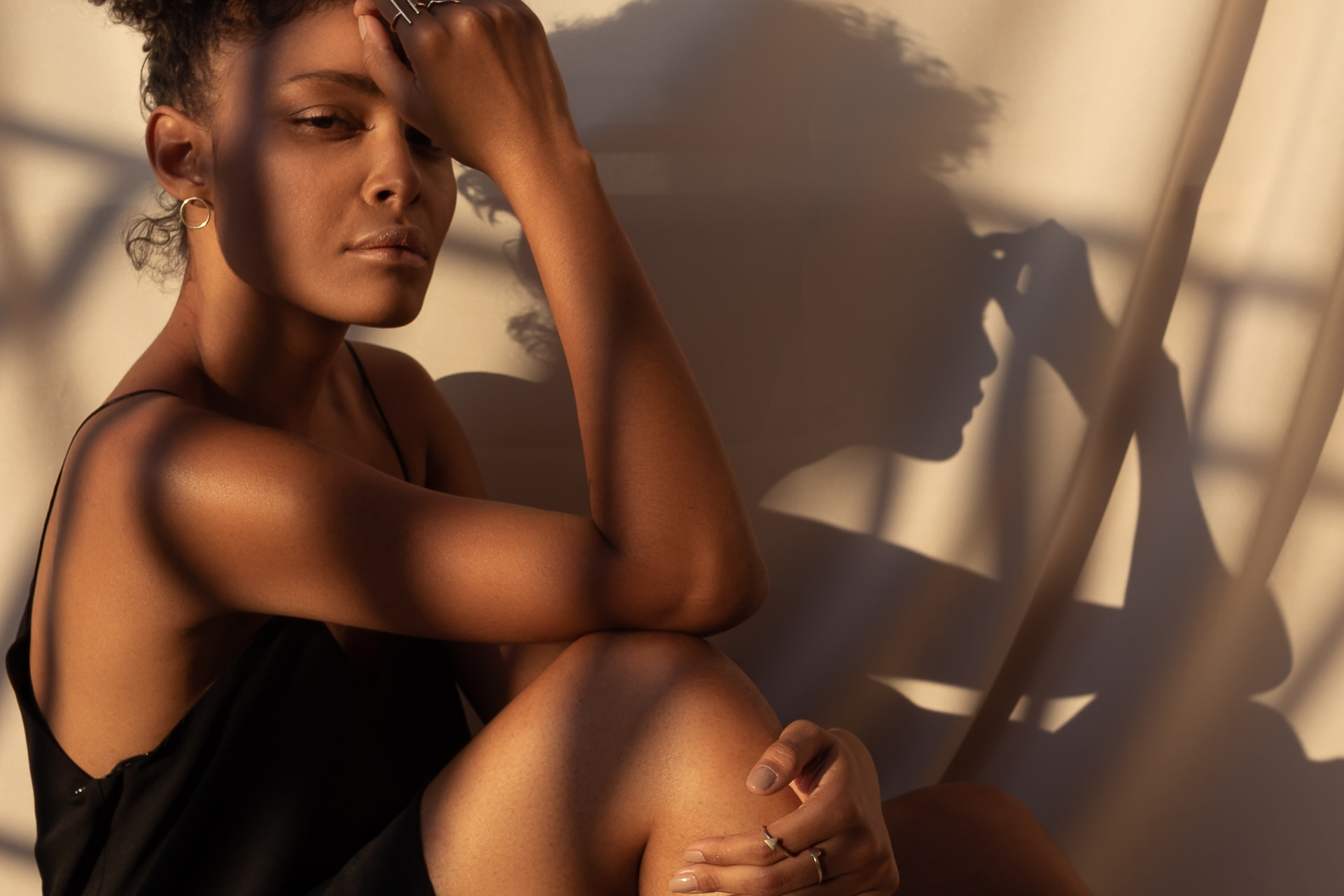 woman wearing black spaghetti strap dress sitting while touching her forehead