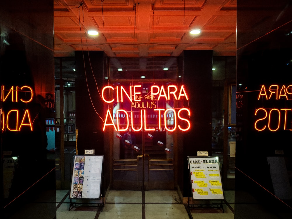 Cine PAra Adultos neon signage in front of closed French doors