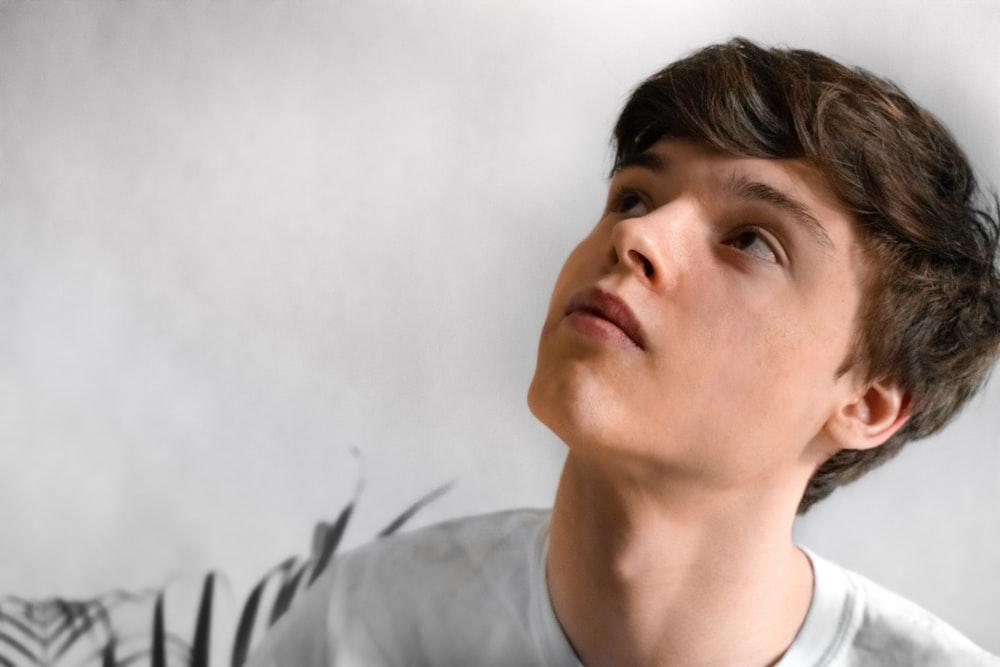 man wearing gray top looking up