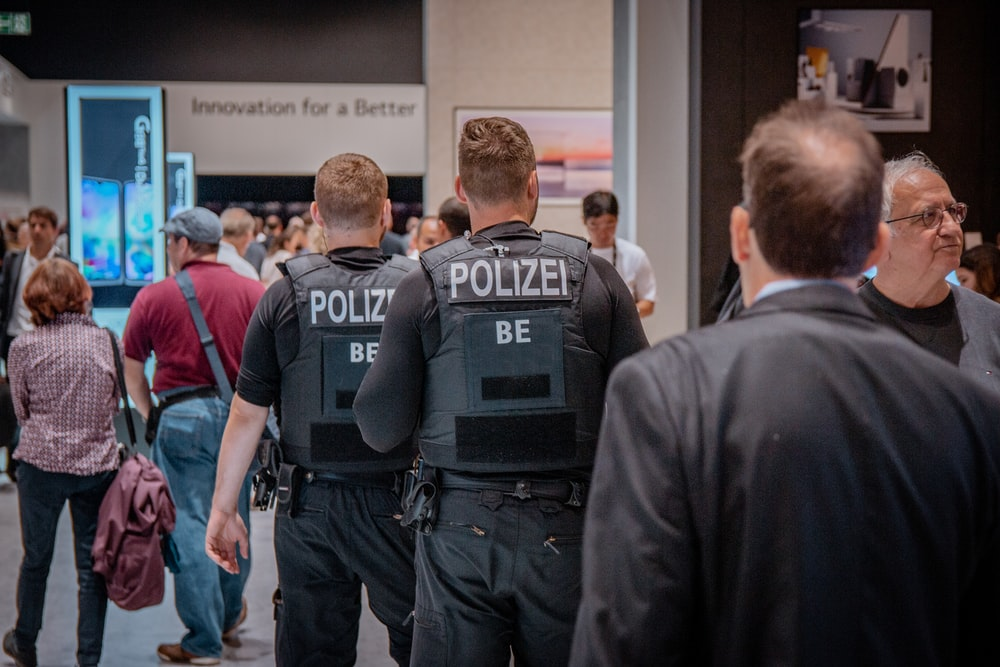 Polize men standing front of people