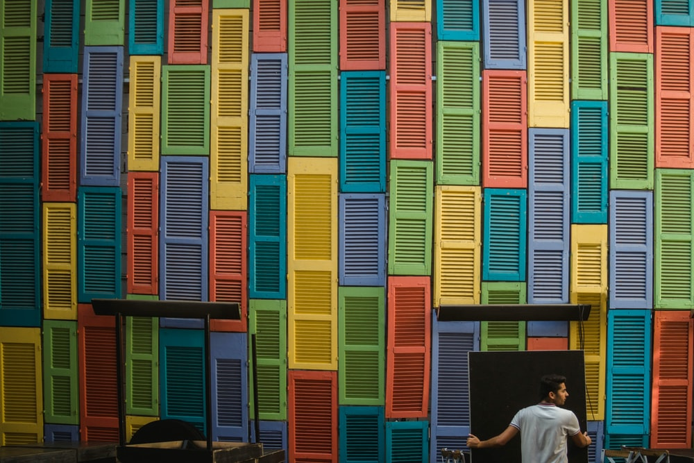 man standing front of m,multicolored wall