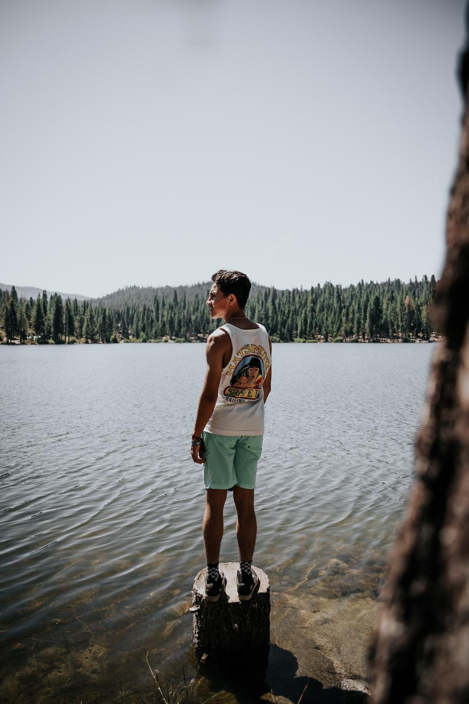 man standing on drift wood