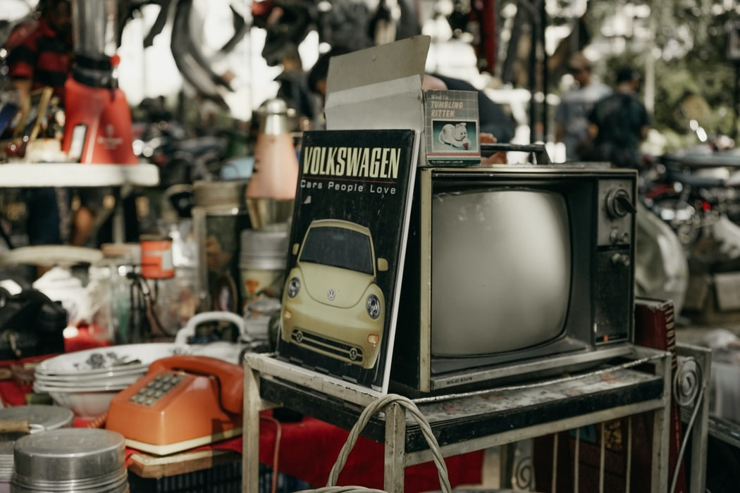 Thrift store with various items on the table including an old television in the foreground, with an old Volkswagen book leaned up against it.