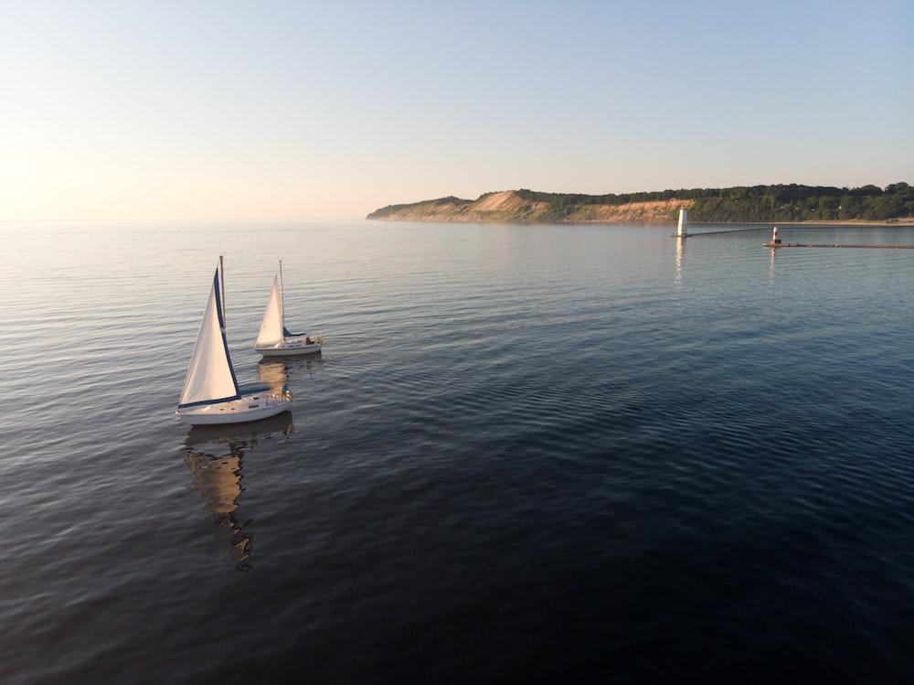 two white sailboats on sea