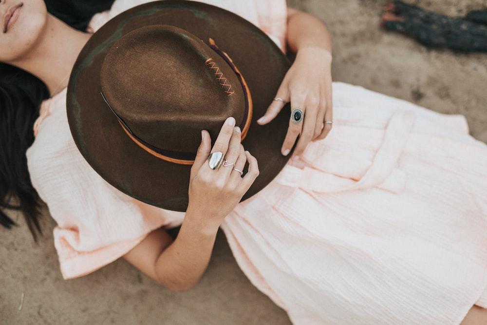 woman wearing pink dress holding brown cowboy hat