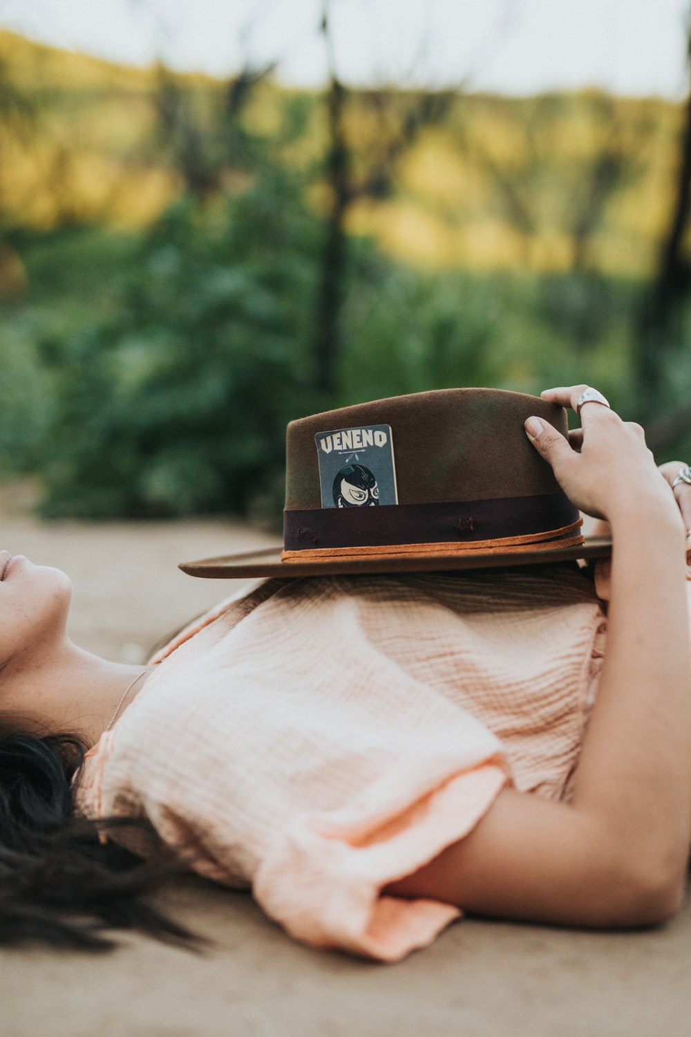 woman wearing beige blouse holding brown fedora hat