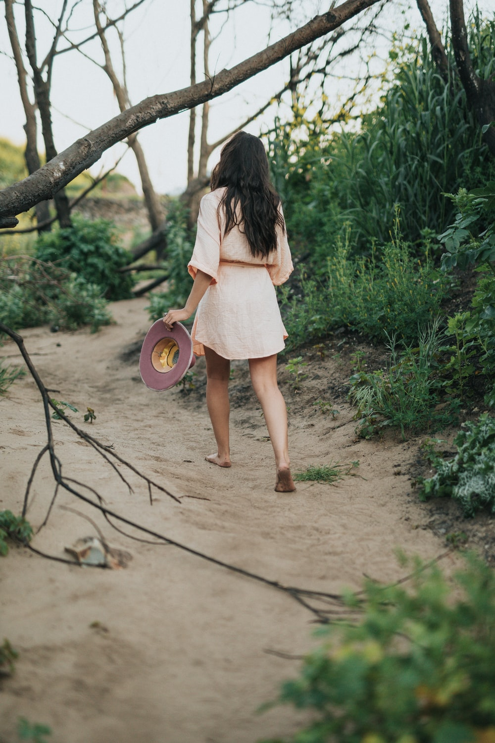 barefoot woman holding hat