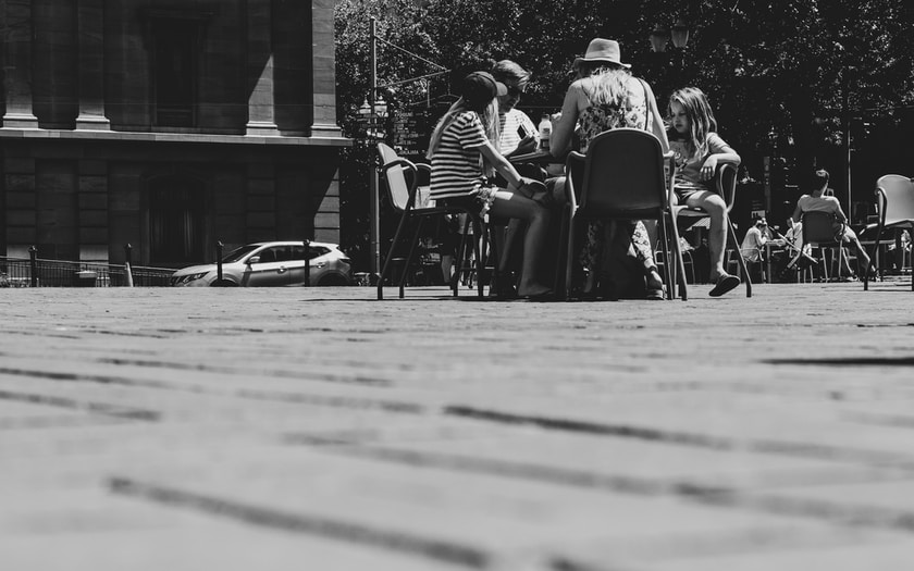 grayscale photo of people sitting at table