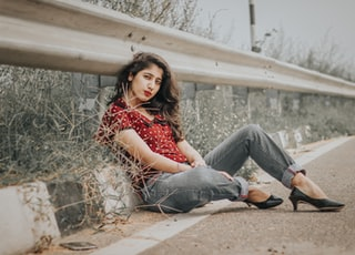 woman in red dotted shirt and gray denim pants sitting on ground near road rail