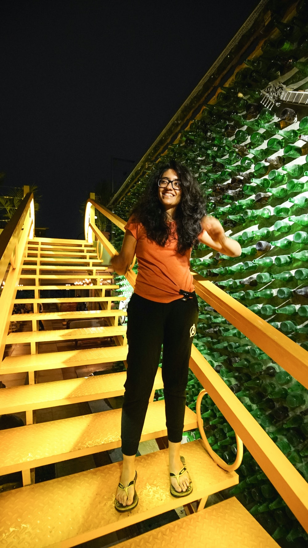 woman in brown top and black pants standing on white stair outdoors