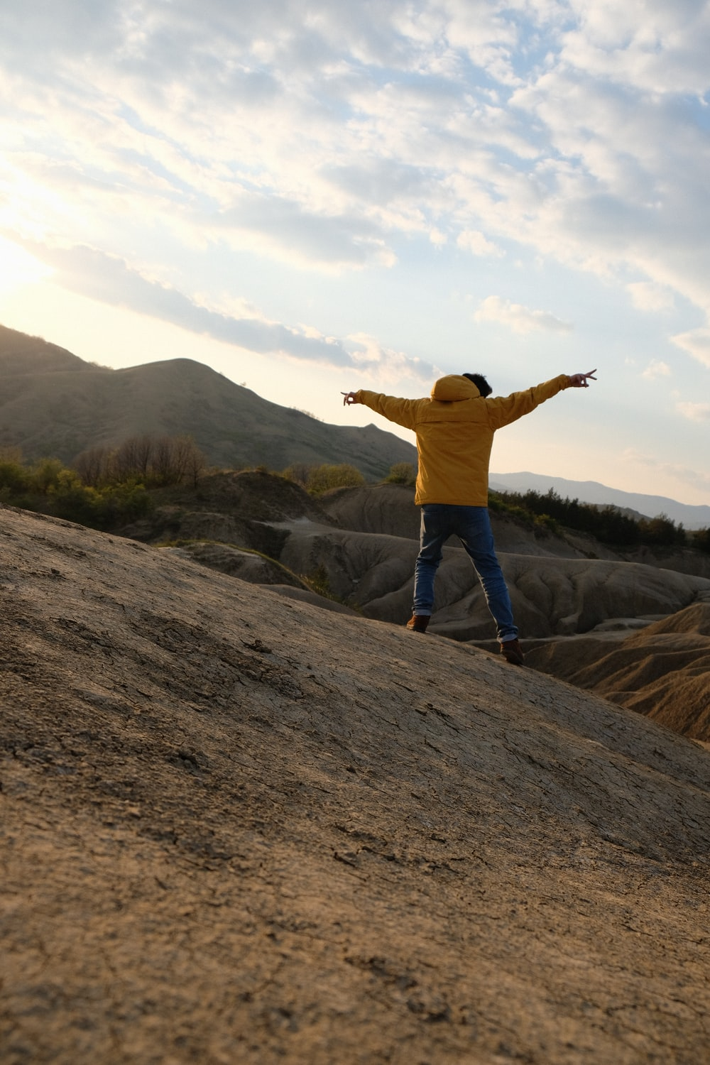 person in yellow hoodie standing on mountain during daytime