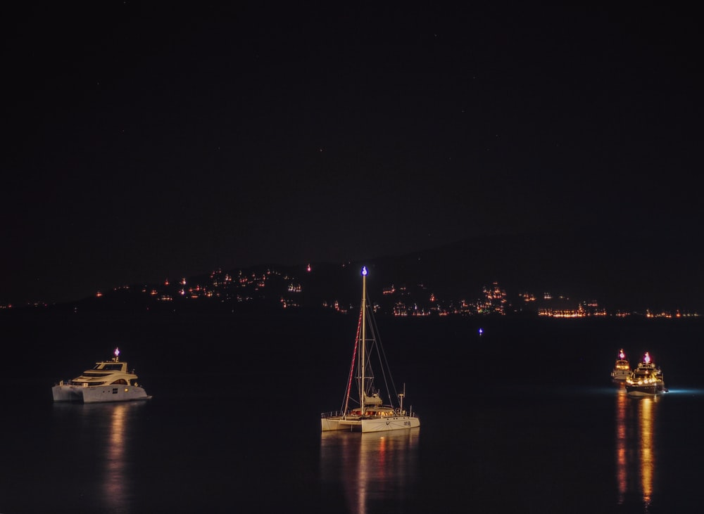several boats floating in the sea during nighttime