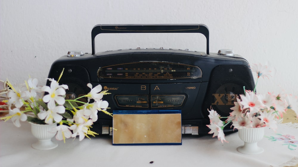 black boombox beside two potted flower arrangements