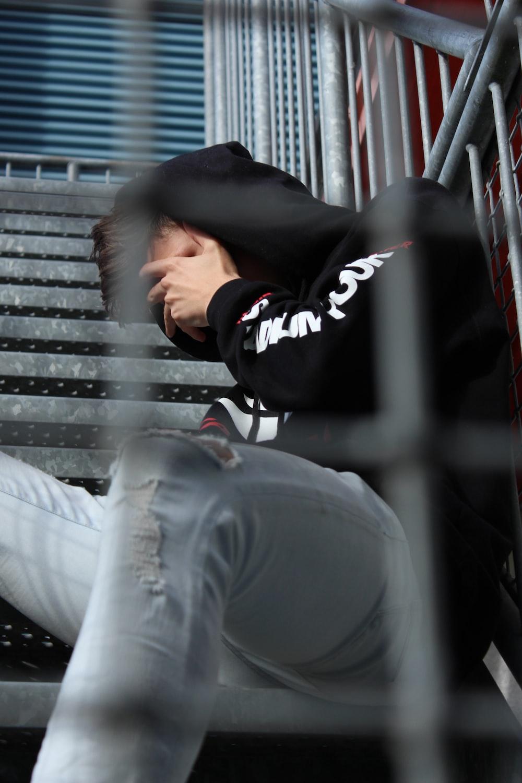 man in black hoodie and blue distressed pants