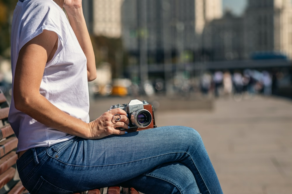 woman sitting on bench and holding camera