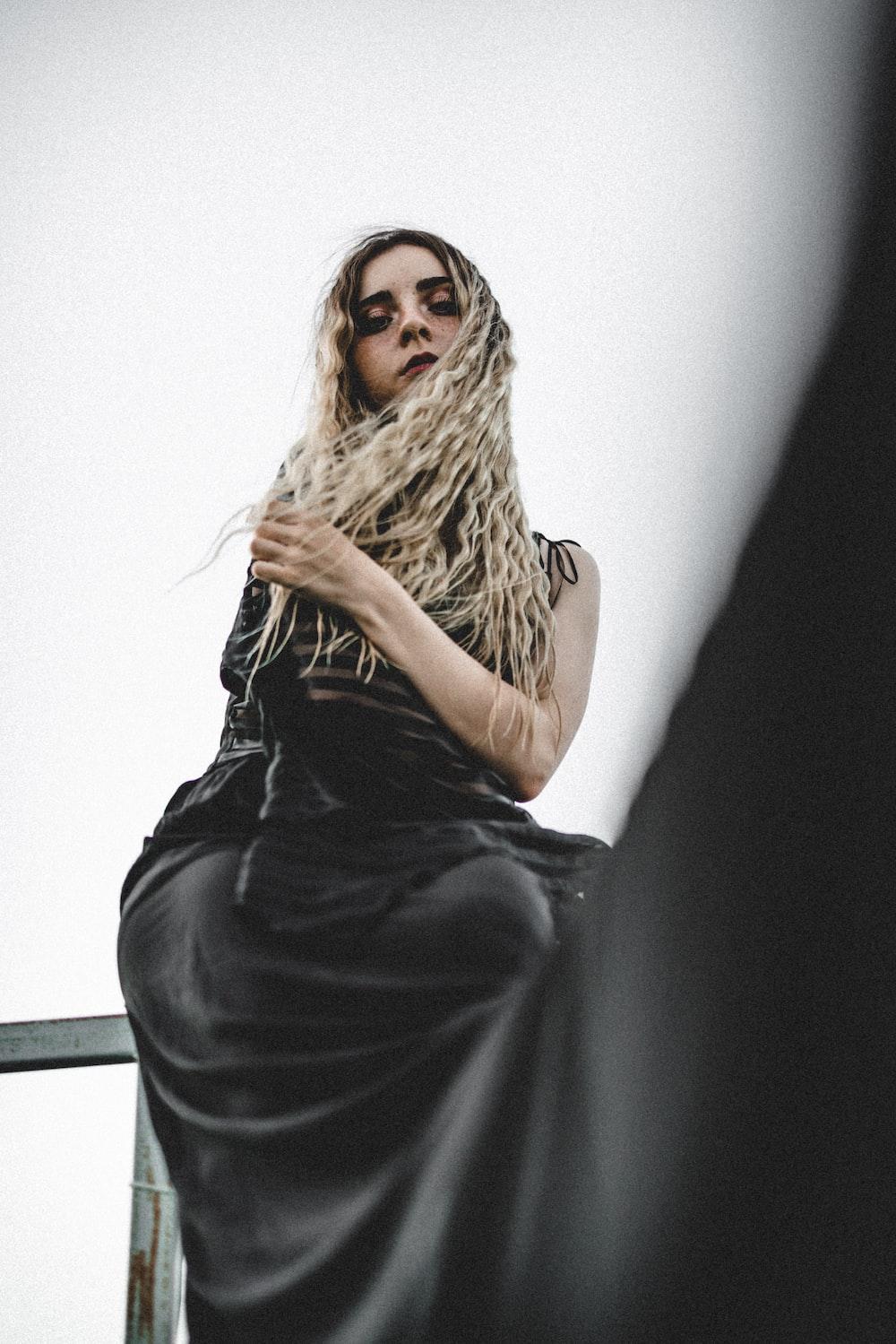 woman wearing black sleeveless dress sitting on railings while looking down