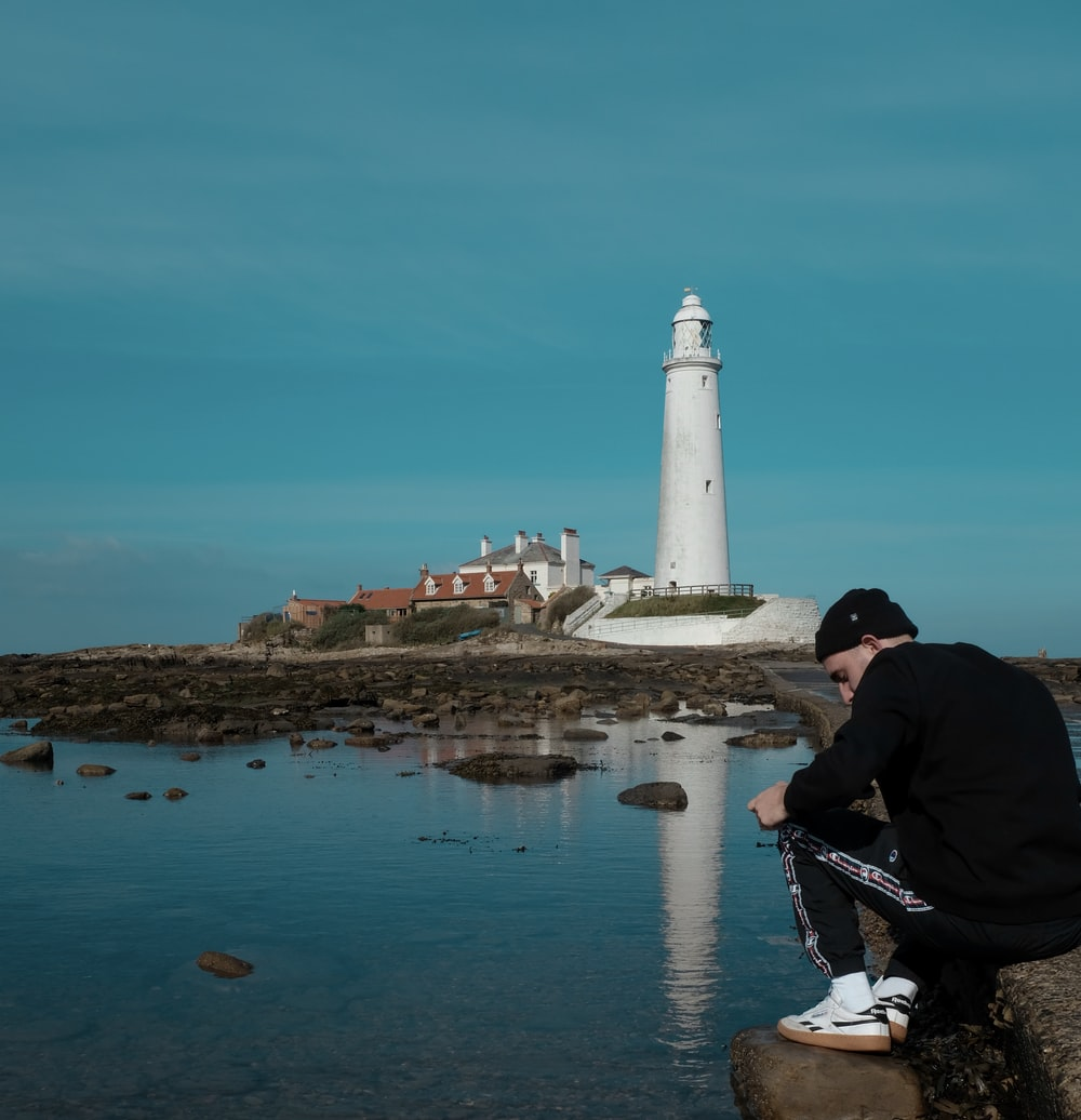 man sitting near lighthouse