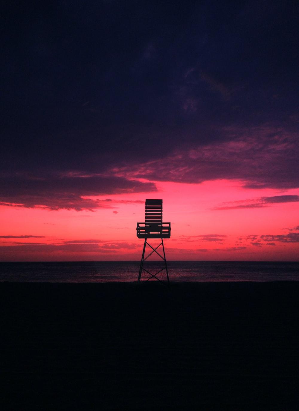 brown watch tower on shore under golden hour