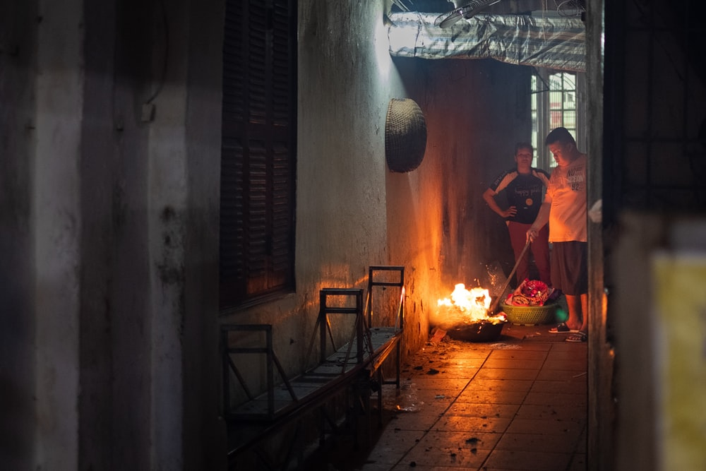 person in orange shirt in front of fire