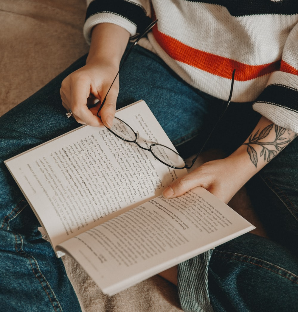 person reading book while holding eyeglasses