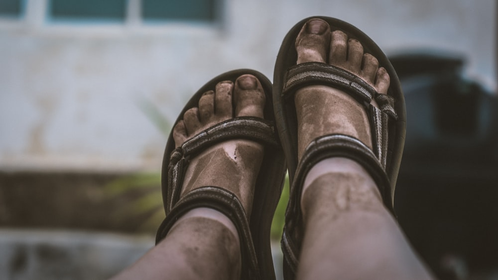 person wearing brown hiking sandals