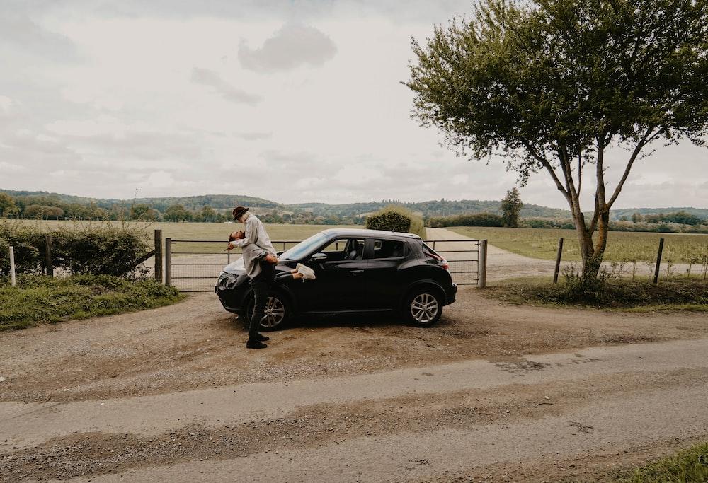man lifting woman beside black Nissan Juke near tree