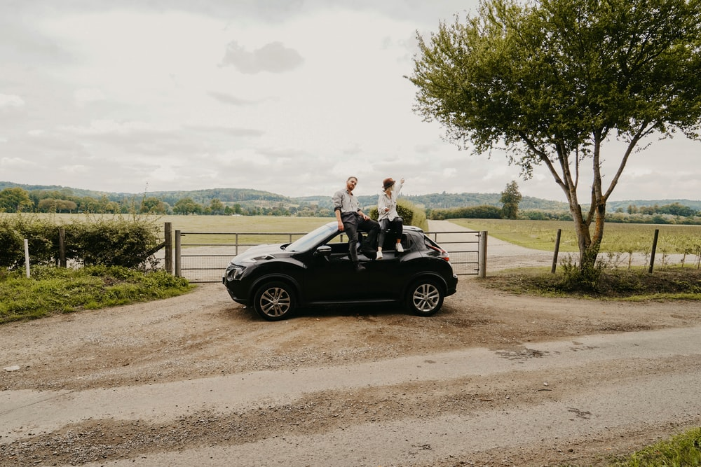 man and woman sitting on top of vehicle near trees