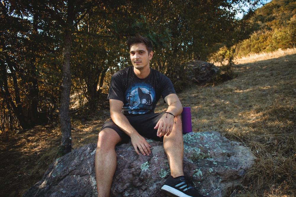 man sitting on stone at adytime