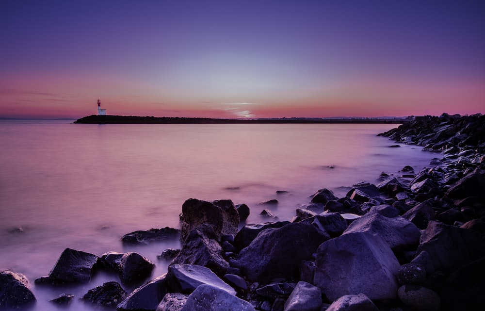 landscape photography of rocky seashore during golden hour