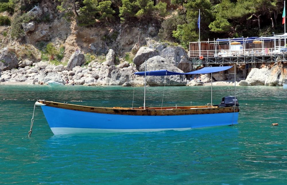 boat floating on body of water near rocky shore