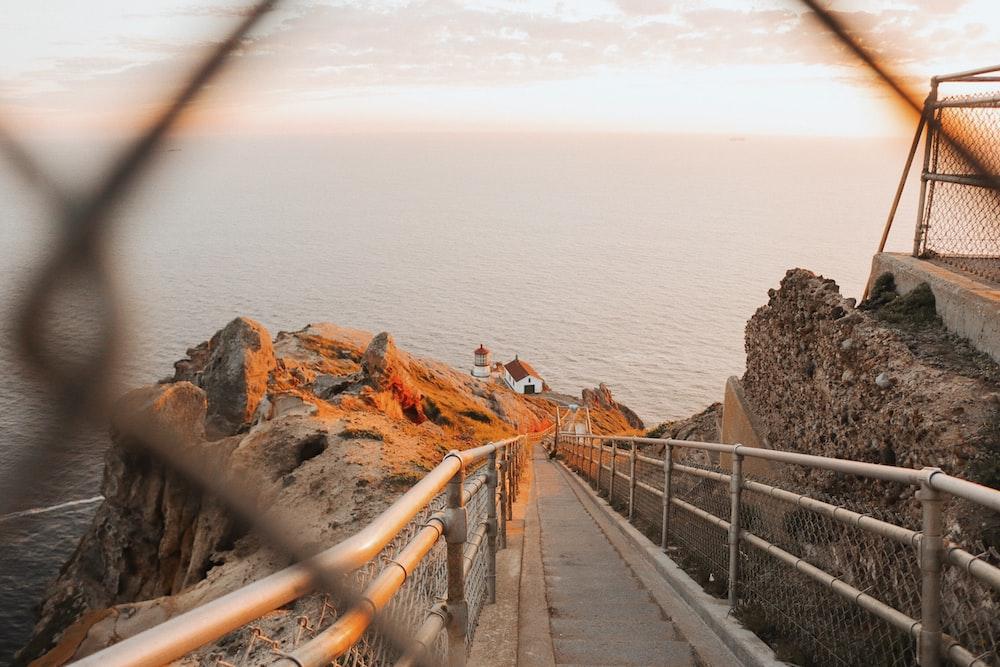 white wooden footbridge viewing sea during daytime