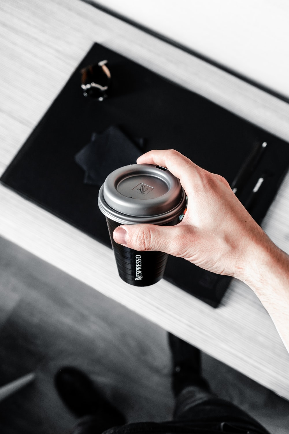 person holding black Nescafe coffee cup with lid