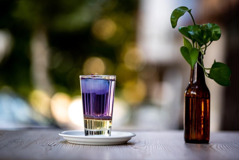 clear shot glass beside amber glass bottle