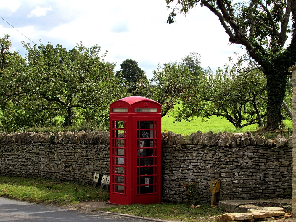 red telephone booth beside brick wall