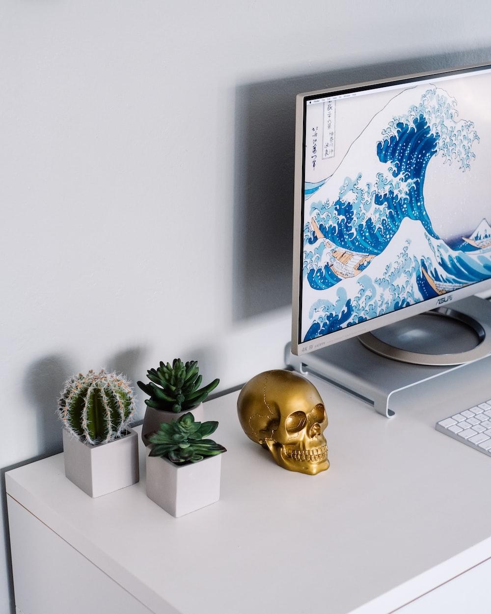 gray flat screen computer monitor beside gold skull ornament