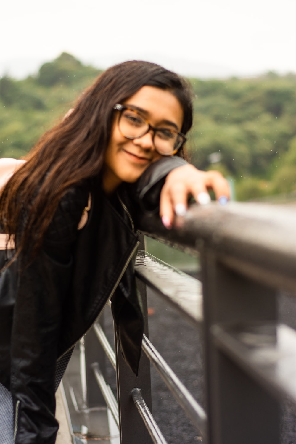 woman wearing jacket and eyeglasses leaning on post smiling