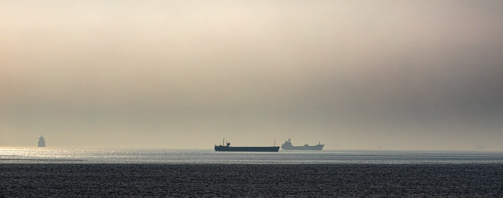 two black and gray ship on sea at daytime
