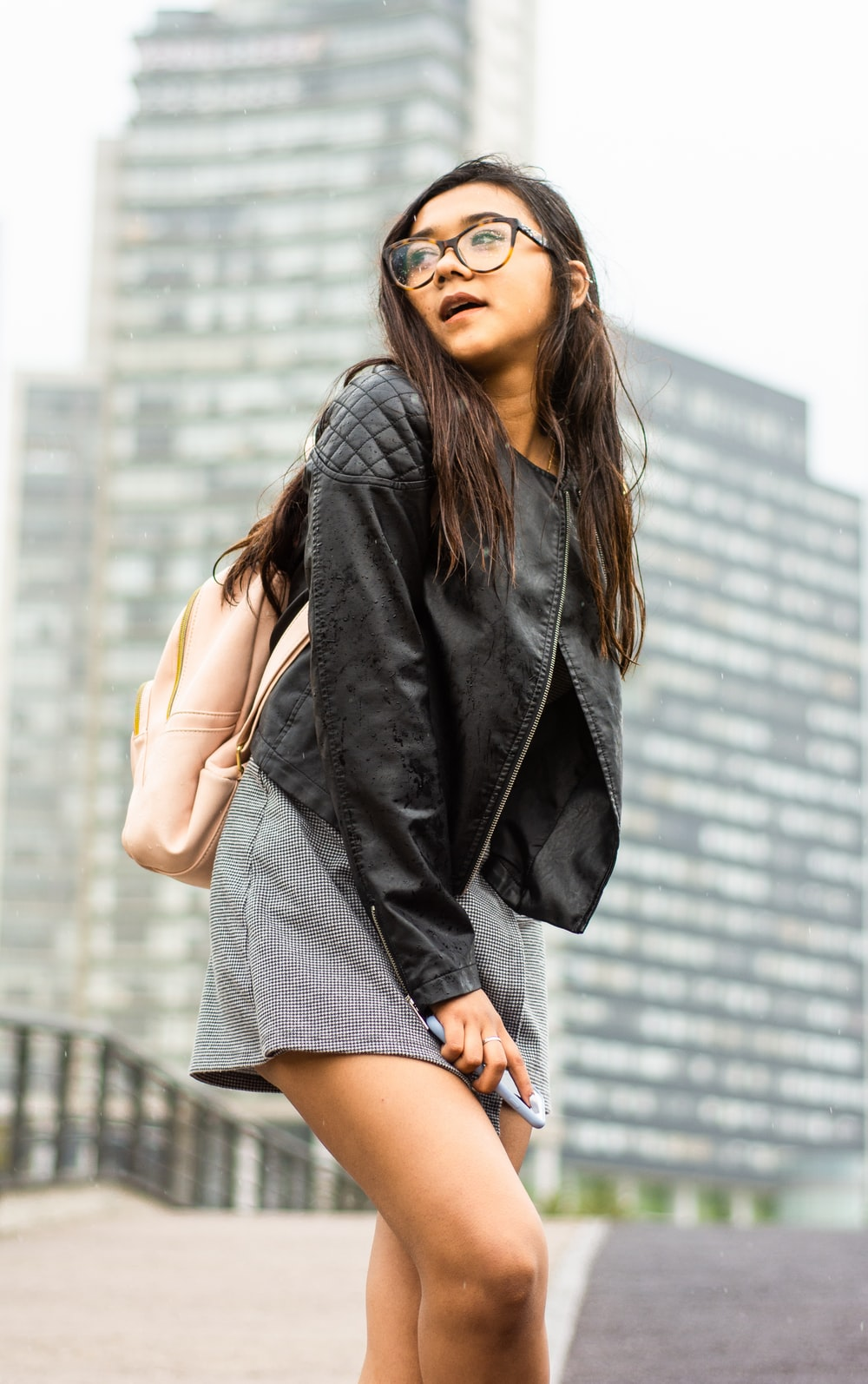 woman in black zip-up jacket and gray skirt