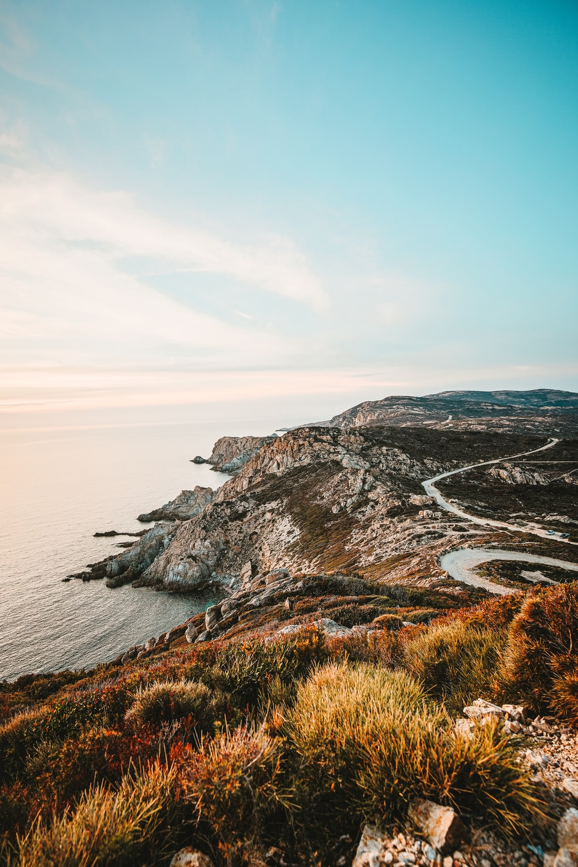 rocky cliff facing ocean under blue sky