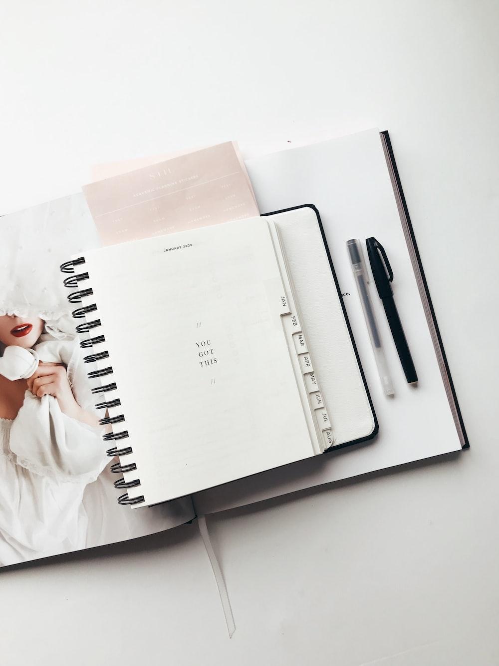 white notebook near pens