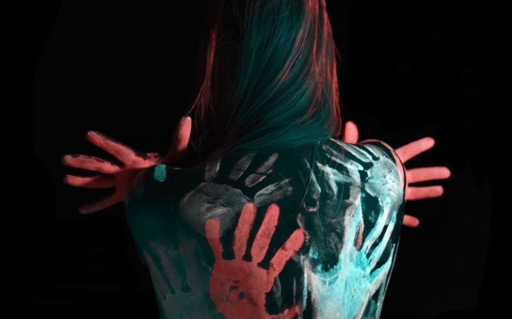 multicolored paint on woman's back