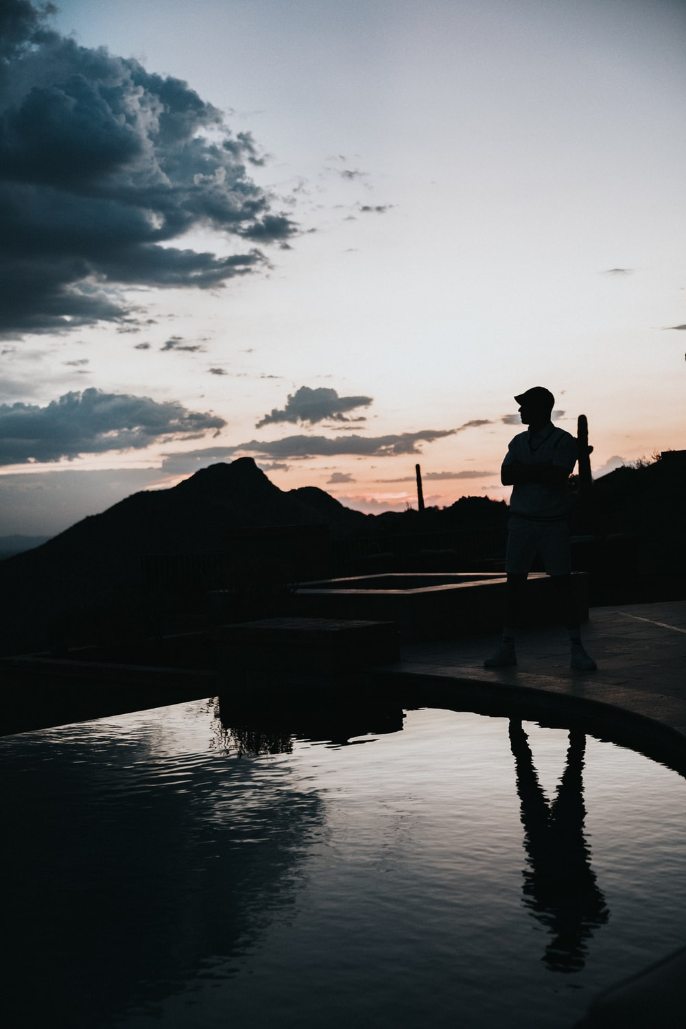 silhouette of man standing in front of pool