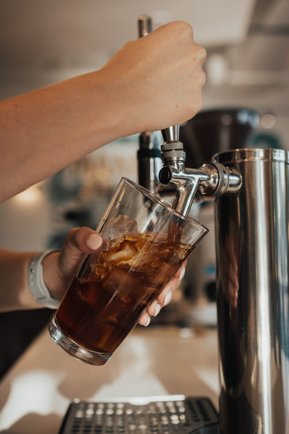 person pouring beverage in clear drinking glass from dispenser